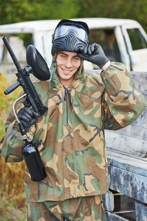 27914192: Happy paintball sport player man in protective camouflage uniform and mask with marker gun outdoors