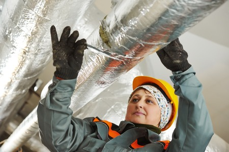 Thermal insulation. Female insulation worker isolating industrial pipe with glass wool and foil Stock Photo