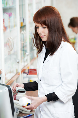 pharmacist chemist woman working in pharmacy drugstore with doctor prescription photo
