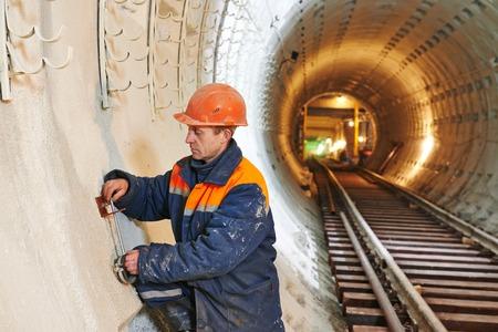 affixment: Tunneller worker installing fixture
