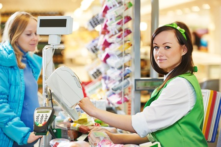 cart cash: Customer buying food at supermarket and making check out with cashdesk worker in store Stock Photo