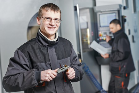 technologist: manufacture technician workers measuring detail and working on metal machining center at factory
