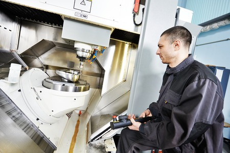 measuring instruments: mechanical technician working at cnc milling machine center in tool workshop