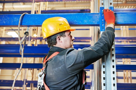an erection: One warehouse worker in uniform during rack erection work installation