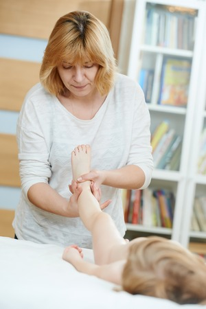 Masseur making a massage to child leg foot and body Imagens