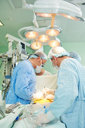 Team of surgeon in uniform perform heart transplantation operation on a patient at cardiac surgery clinic