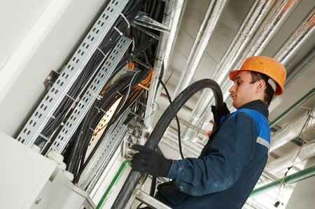 electrician builder engineer installing industrial cable into fuse box Stock Photo