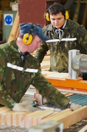 Workers of woodworking manufacture operating on machine photo