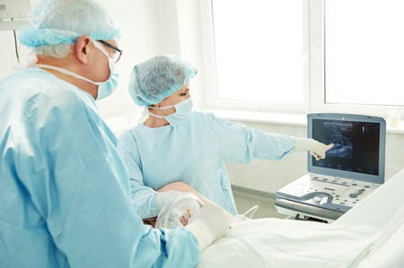 varicose veins: Team of surgeon in uniform perform varicose veins correction operation on a patient at surgery clinic Stock Photo