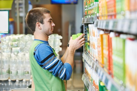Merchandising. Sales assistant in supermarket lay out goods on supermarket shelves at store Stock Photo