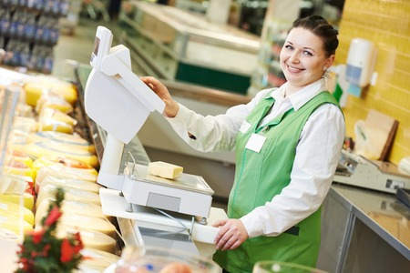 Smiling saleswoman assistant in supermarket working with scales balance to pregnant female customer during shopping at store photo