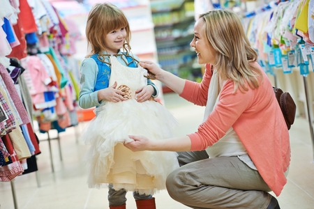 woman and little girl choosing and trying on dress clothes during shopping at garment supermarket Stock Photo