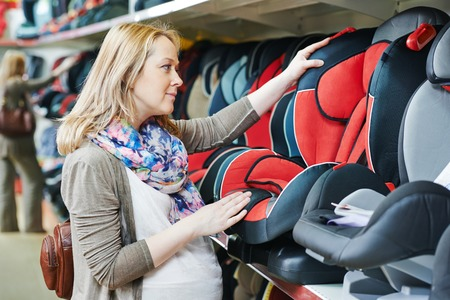 woman choosing child car seat for newborn baby in shop supermarket photo