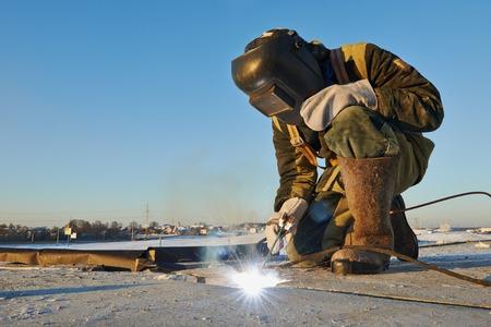 soldador: soldador de trabajo con el electrodo en la soldadura de arco en invierno obra de construcción al aire libre Foto de archivo