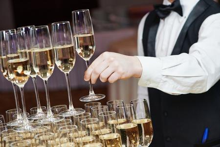 Ober hand met glas champagne over piramide tijdens catering bij partij