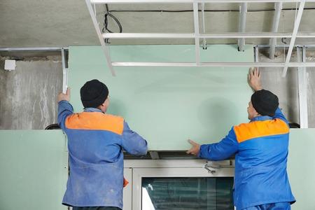 plasterboard: Carpenter joiner plasterer with screwdriver mounting gypsum plasterboard system at toilet