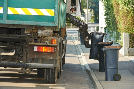 urban municipal recycling garbage collector truck loading waste and trash bin Stock Photo