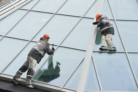 Two male industrial builders workers at outdoors window installation