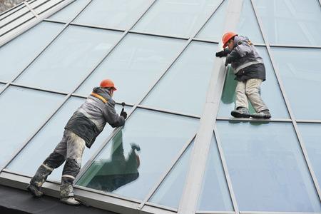 Zwei männliche Industriearbeiter an Bauherren im Freien Fenstereinbau Standard-Bild