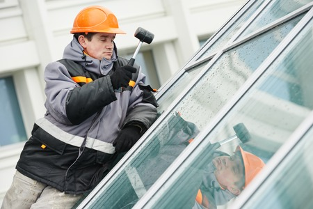 fixing: male industrial builder worker at window installation