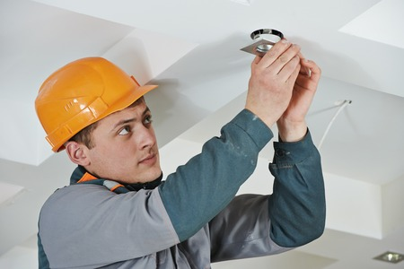 replacing: electrician worker in uniform installing or replacing spot light lamp into ceiling