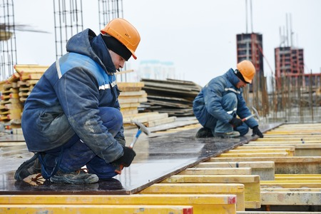 building activity: construction worker at construction site assembling falsework for concrete pouring