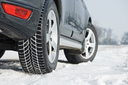 manejando: Coche con neumáticos de invierno instalados en llantas de aleación ligera en camino al aire libre cubierto de nieve Foto de archivo