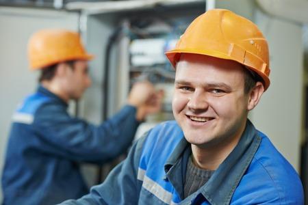 Fuseboard で、彼の同僚のねじ装置の前で幸せな若い大人の電気技師ビルダー エンジニア