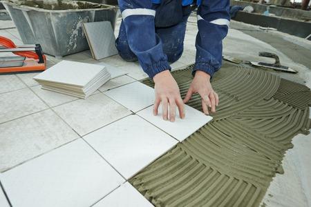 industriële tegelzetter bouwer werknemer installeren vloertegel op reparatie renovatie Stockfoto