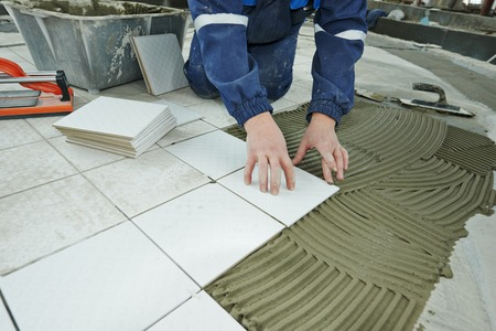 tiling: industrial tiler builder worker installing floor tile at repair renovation work