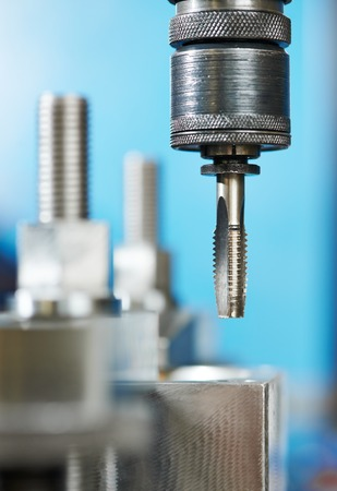 Close up machining tool thread former tap during metal cutting process