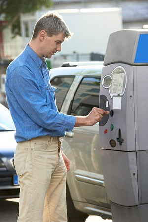 young man paying at parking meter photo