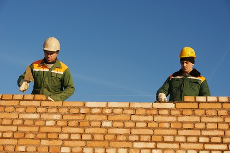 sand lime bricks: two construction mason worker bricklayer installing red brick with trowel putty knife outdoors Stock Photo