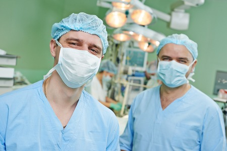 happy surgeons in uniform perform heart transplantation operation on a patient at cardiac surgery clinic Stock Photo