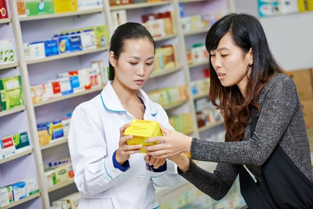 medications: Two cheerful chinese pharmacist chemist woman standing in china pharmacy drugstore