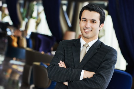 Portrait of a young businessman in suit standing at hotel interior Stock Photo