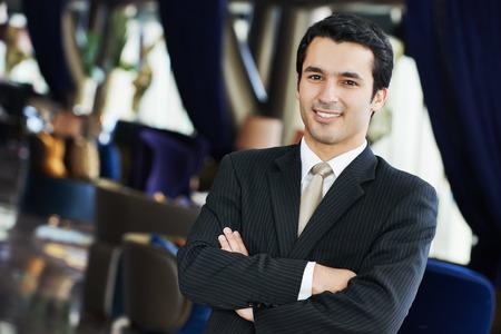 gerente: Retrato de un joven hombre de negocios en traje de pie en el interior del hotel Foto de archivo