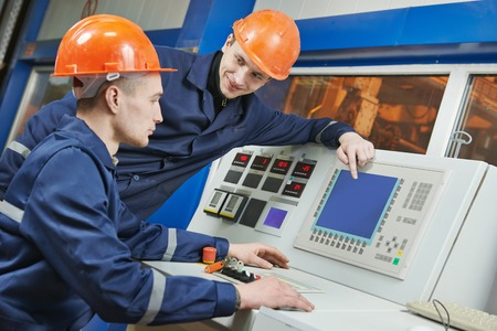 operative: two operative industrial engineer workers discussing manufacture process near control panel system Stock Photo