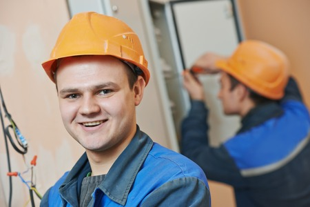screwing: Happy young adult electrician builder engineer in front of his co-worker screwing equipment in fuseboard