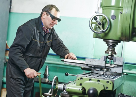 operative: milling machine operator working in factory workshop