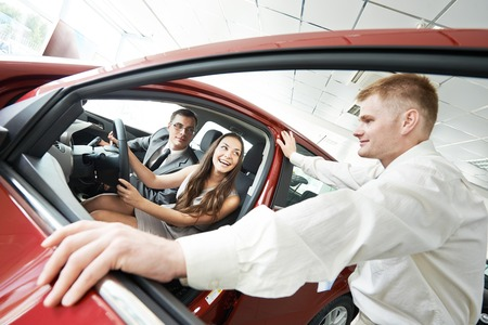 automobile dealer: Car salesperson demonstrating new automobile to young woman Stock Photo