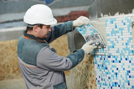 tegelwerk: industriële tegelzetter bouwer werknemer installeren vloertegel op reparatie renovatie