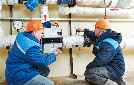 boiler house: two repairman engineer of fire engineering system or heating system open the valve equipment in a boiler house Stock Photo