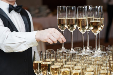 Waiter hand with glass of champagne over pyramid during catering at party