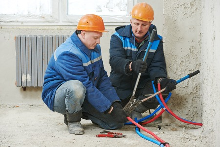 two repairman engineer installing house heating system at interior construction site photo