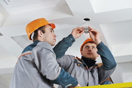 electrician worker in uniform installing or replacing spot light lamp into ceiling photo