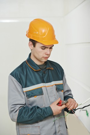 wirework: electrician worker in uniform working with cable wiring