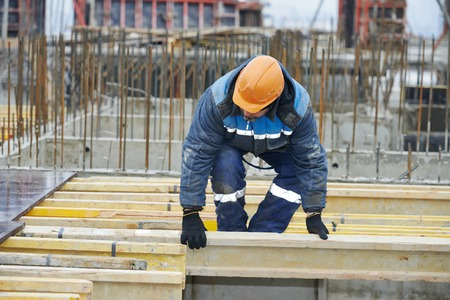 construction worker at construction site assembling falsework for concrete pouring photo