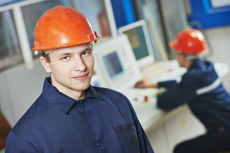 portrait of positive adult industrial worker at factory workshop photo
