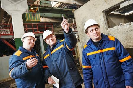 fettler: tres jefe ingeniero industrial discutir el desarrollo de empresas en la construcci�n de planta de la casa Foto de archivo